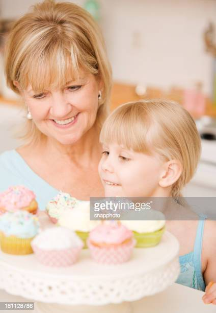 Child and Mature Woman Eating Cupcakes