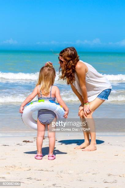 Child and mom standing on beach
