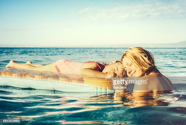 Child and mother on inflatable mattress sunbathing on blue sea