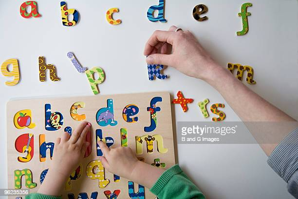 Child and Mother Play with Coloured Letters