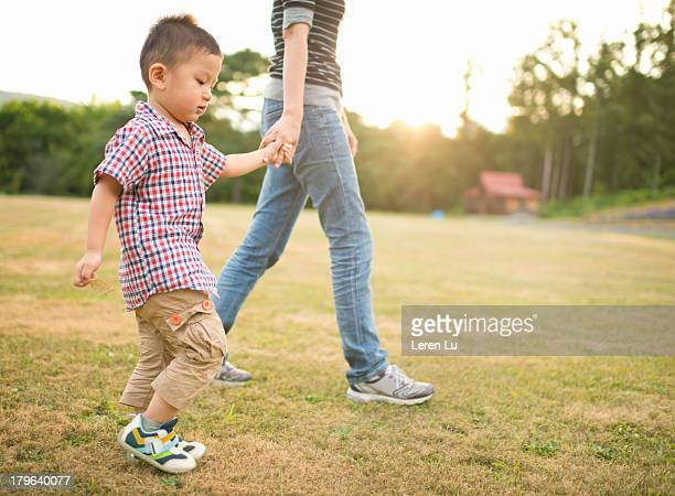 Child and mother walking on grass under sunset.