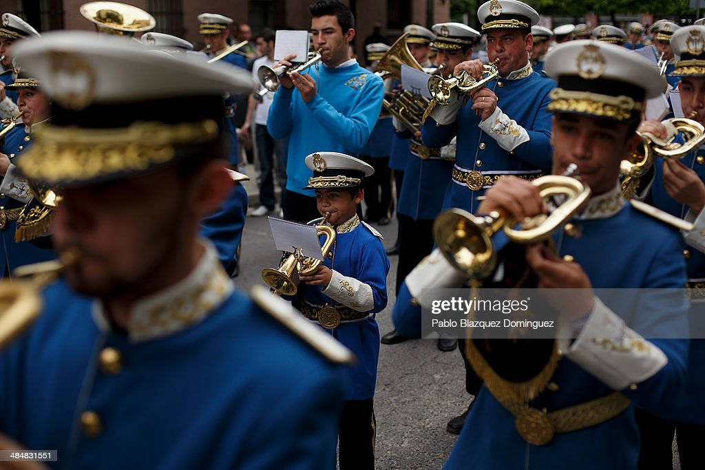 A child and other members of music band from 'Santa Genoveva' brotherhood play music during a procession on April 14, 2014 in Seville, Spain. Easter week is traditionally celebrated with processions in most Spanish towns.