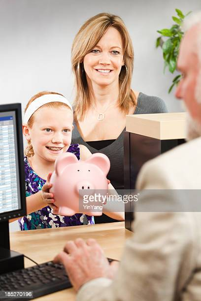 Child and Parent Taking Saving to Retail Bank Teller Counter