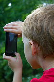 child makes photo on the phone,  young boy and smartphone
