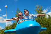 child girl and boy fly on blue plane attraction in city park, happy childhood, summer vacation concept