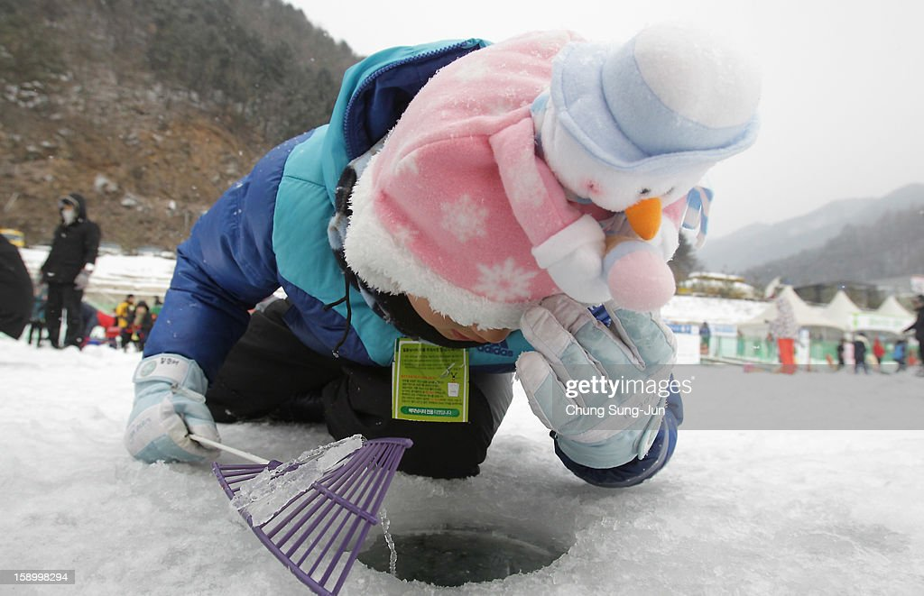 A child angler looks through a hole into a frozen river during an ice fishing competition at the Hwacheon Sancheoneo Ice Festival on January 5, 2013 in Hwacheon-gun, South Korea. The annual event attracts thousands of visitors and features a mountain trout ice fishing competition in which participants compete with tradition lures or with bare hands.