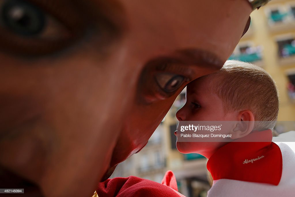 A child approaches to kiss the King Giant figure during the farewell ceremony of the Comparsa de Gigantes y Cabezudos 'Giants and Big Heads parade' at the Town Hall Square on the final day of the San Fermin Running Of The Bulls festival on July 14, 2014 in Pamplona, Spain. The annual Fiesta de San Fermin, made famous by the 1926 novel of US writer Ernest Hemingway 'The Sun Also Rises', involves the running of the bulls through the historic heart of Pamplona.