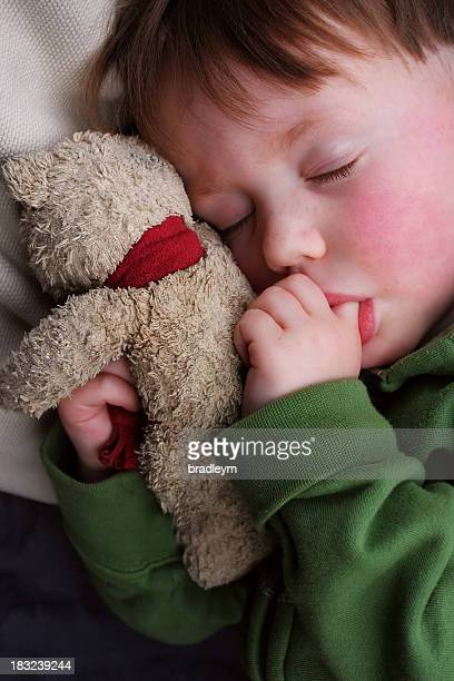 Child asleep with teddy bear, with thumb in mouth