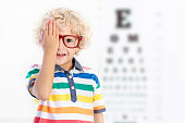 Child at eye sight test. Little kid selecting glasses at optician store. Eyesight measurement for school kids. Eye wear for children. Doctor performing eye check. Boy with spectacles at letter chart.