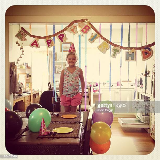 Child at party standing beneath a birthday banner