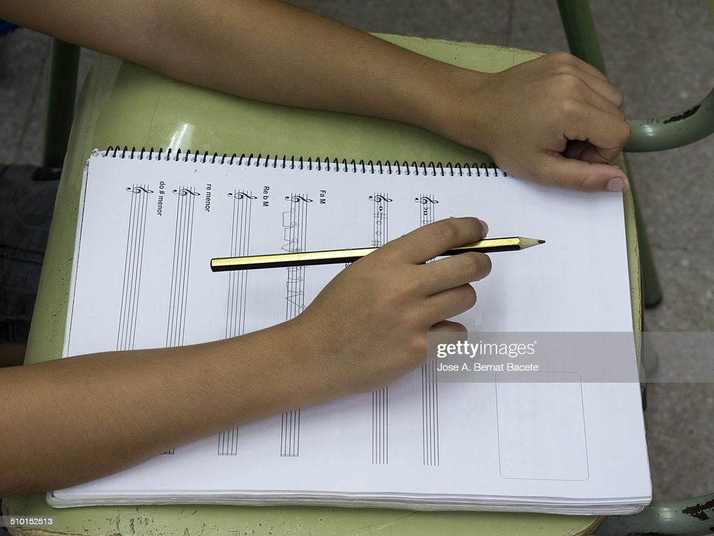 Child at school writing on a notebook of music