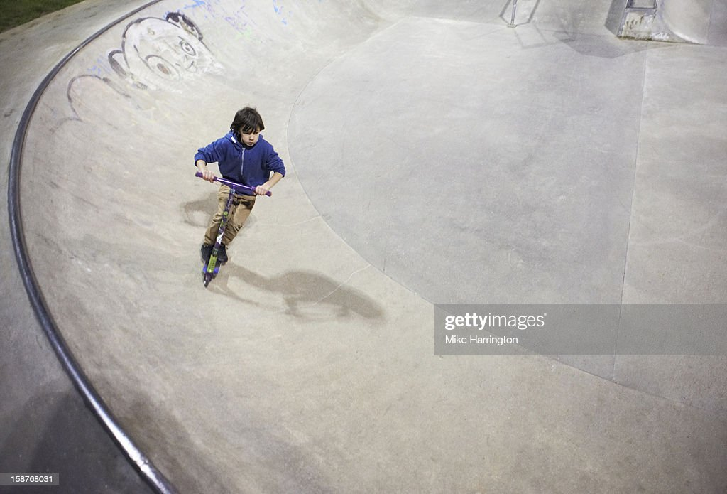 Child at skate park riding micro scooter. : Stock Photo