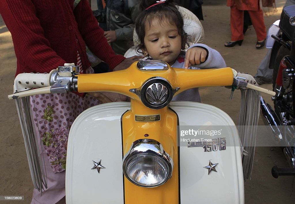 A child at the Vintage Lambretta -150 scooter during the '21 Gun Salute Vintage Rally' on December 9, 2012 in New Delhi, India.