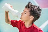 Child athlete drinking water