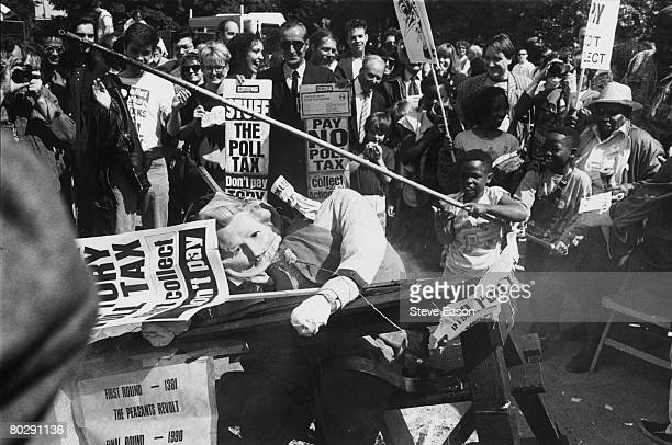A child attacking an effigy of Margaret Thatcher during an anti poll tax demonstration in Hackney London 27th May 1990