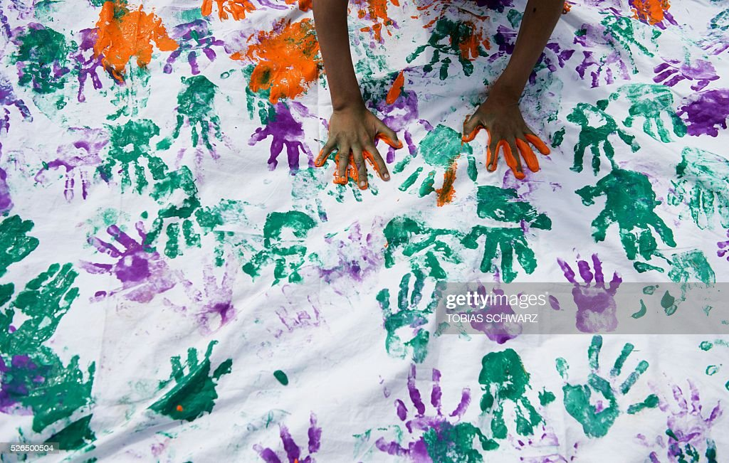 A child attends an artwork project by marking a white sheet of painted handprints at a makeshift camp for migrants and refugees near the village of Idomeni not far from the Greek-Macedonian border on April 30, 2016. Some 54,000 people, many of them fleeing the war in Syria, have been stranded on Greek territory since the closure of the migrant route through the Balkans in February. / AFP / TOBIAS