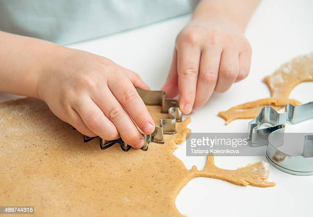 Child baking ginger cookies for Christmas