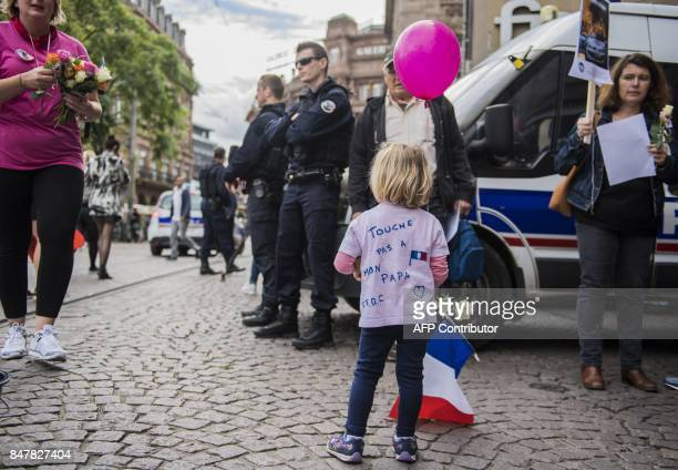 A child bearing a sign reading 'Don't touch my daddy' stands next to policemen during a protest of law enforcement's wives and relatives to ask the...