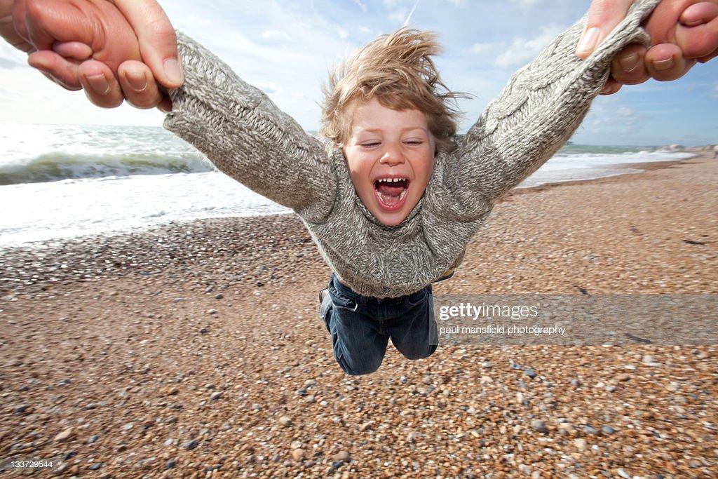 Child being swung around on beach