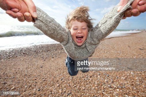 Child being swung around on beach