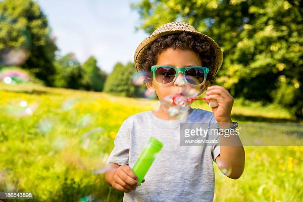 Child blowing bubbles in park