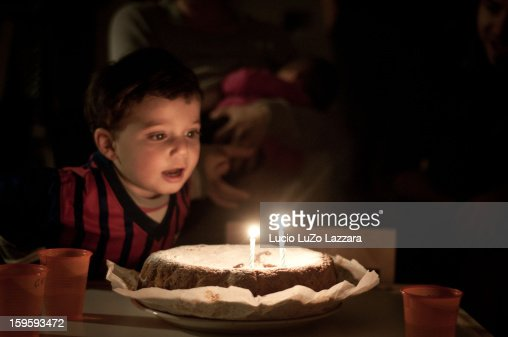 Child blowing candles on 2nd birthday : Stock Photo