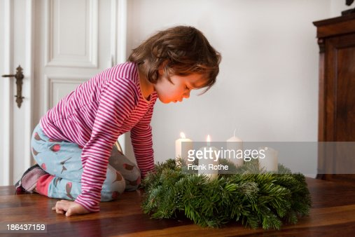 Child blowing out advent candle