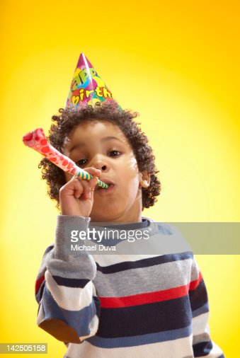 child blowing party favor paper horn for birthday : Stock Photo