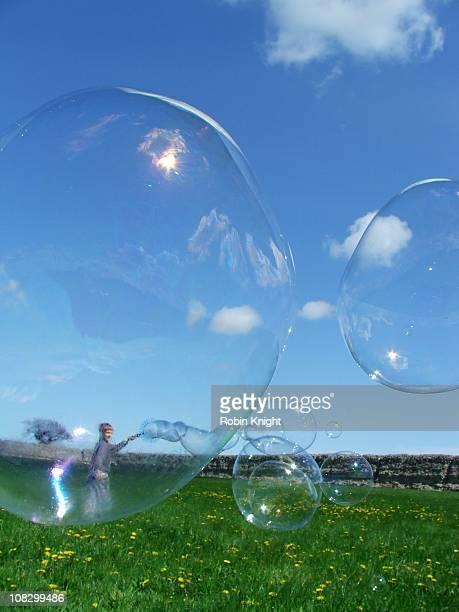 Child blows large soap bubbles