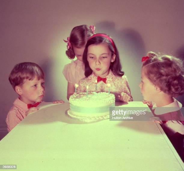A child blows out the candles on her birthday cake