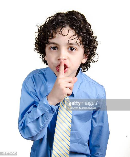 Child boy doing shushing sign the serious boy in a shirt and tie put a finger to his lips and shows sign quieter