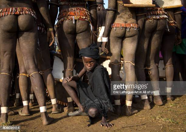 Child boy in the middle of Bodi tribe fat men legs during Kael ceremony Omo valley Hana Mursi Ethiopia on June 4 2017 in Hana Mursi Ethiopia