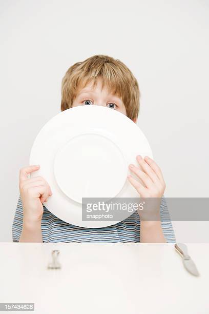 Child Boy with Knife and Fork Licking  Dinner Plate
