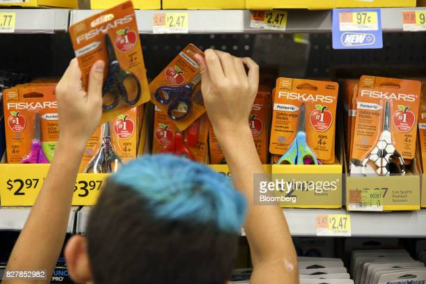 A child browses Fiskars OYJ ABP scissors school supplies displayed for sale at a WalMart Stores Inc location in Burbank California US on Tuesday Aug...
