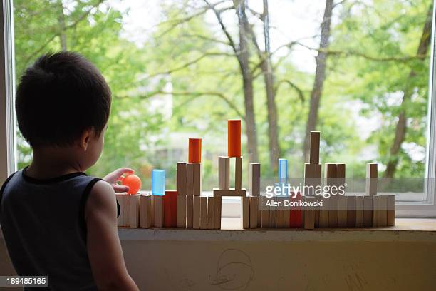 Child building tower with blocks on window sill
