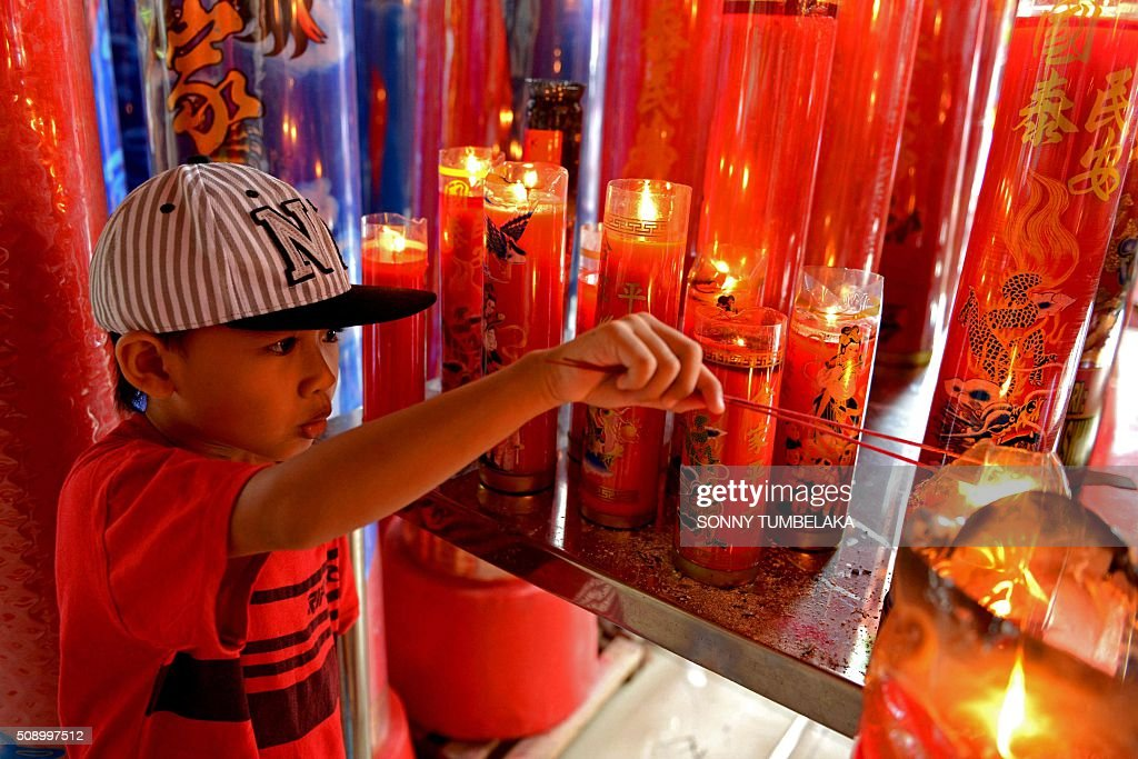 A child burns incense sticks before offering prayers on the first day of the Lunar New Year of the Monkey at the Dharmayana temple in Kuta, near Denpasar on Indonesia's Bali island on February 8, 2016. The Lunar New Year is celebrated in many parts of the predominantly Muslim country of 250 million people where Chinese heritage took roots through ancient transmigration. AFP PHOTO/SONNY TUMBELAKA / AFP / SONNY TUMBELAKA
