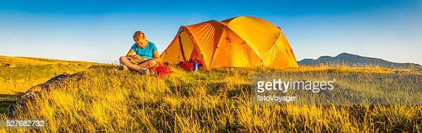 Kind Camping in einer idyllischen Lage am Berg Wiese Sommer Sonnenuntergang panorama, Schottland