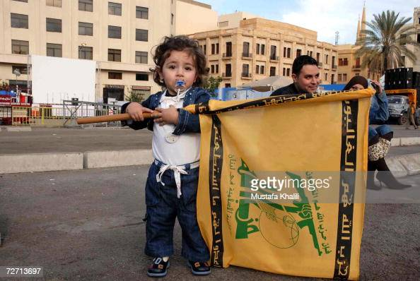 A child carries a flag as demonstrators gather for a fourth day in Martyr's Square December 4 2006 in downtown Beirut Lebanon Opposition...