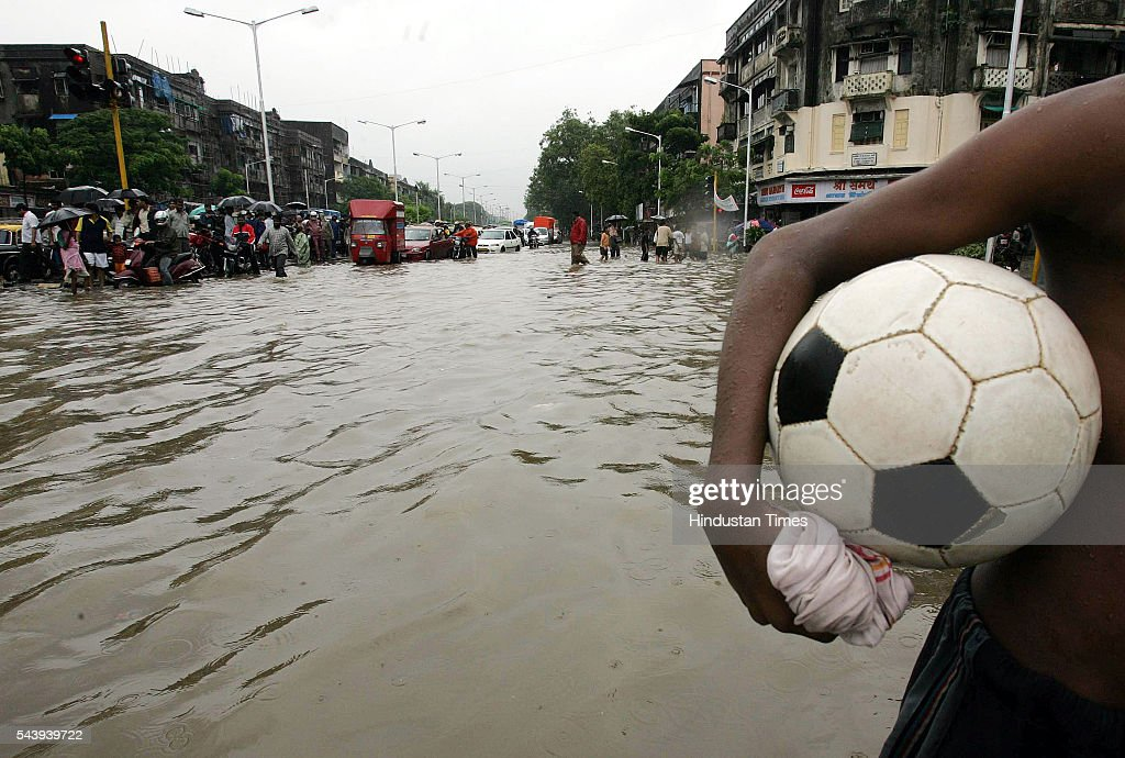 A child carries a football in his hand while wading through the flooded streets near Hindmata Cinema, Parel, after heavy rains lashed across Teh City on July 21, 2005 in Mumbai, India. Heavy rains lashed across the city leaving most of the areas around the city in a flooded state.