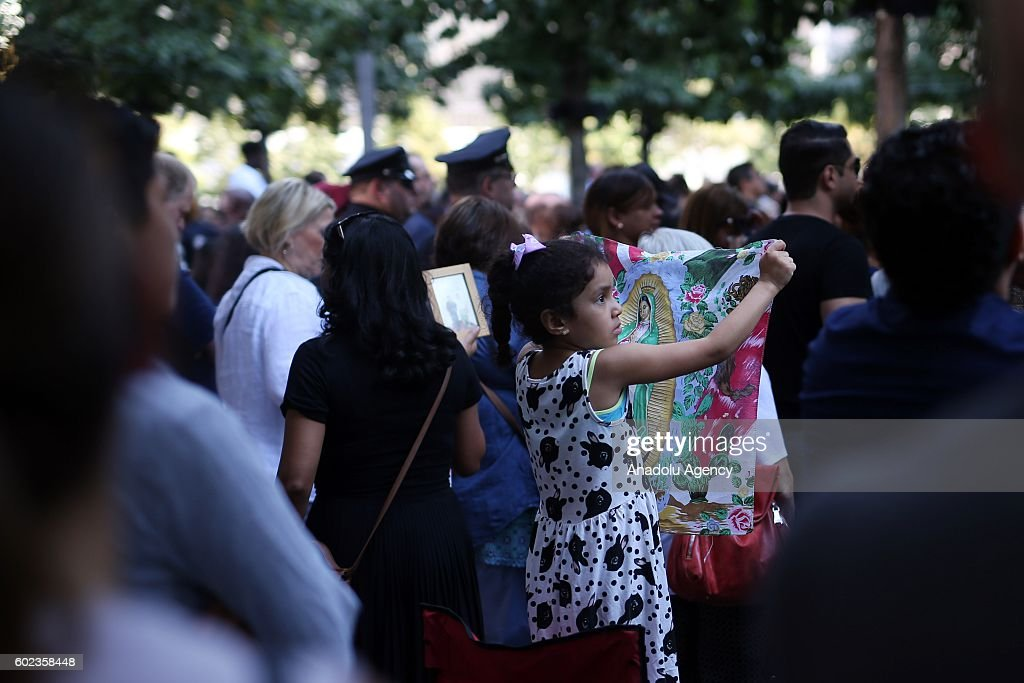 A child carries a photo of Virgin Mary on the 15th anniversary of the 9/11 in Ground Zero, Manhattan, New York, United States on September 11, 2016.