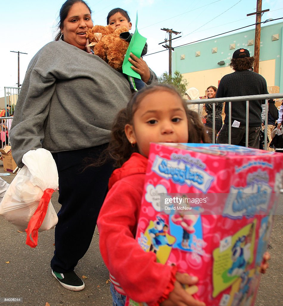 A child carries her new toy as people receive gifts of food, personal care and household items and toys at the Miracle in South Central event, part of the nationwide Miracle on Main Street, USA program to help working poor and disadvantaged families on December 13, 2008 in the South Central neighborhoods of Los Angeles, California. About 5,000 families are expected to receive enough food at the event to supplement meals for a family of four for a week. Miracle on Main Street, USA is sponsored by The National Basketball Players Association (NBPA) along with Feed The Children, Feed 333, Humanity Unites Brilliance (HUB) and hosted by the Salvation Army.