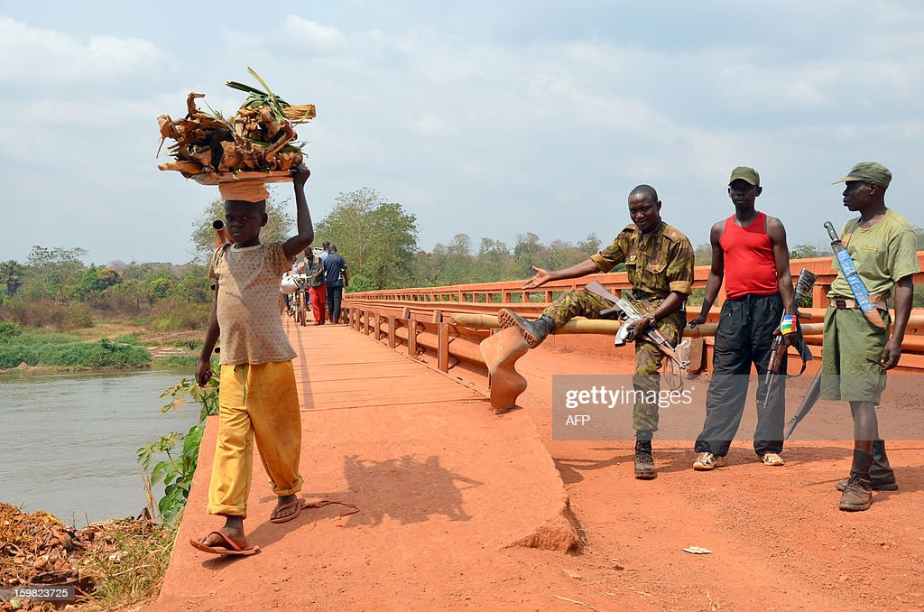 A child carrying goods on his head crosses a bridge over the Ouaka river in Bambari as lieutenant Oscar Amin , aka 'Jack Bauer', motions to pass on January 20, 2013. Rebels hold the town and demand a toll from any vehicle wanting to cross though pedestrians have free passage. Bambari, a former military stronghold, was seized last month by rebels, who have taken control of a string of major regional cities and were inching towards the capital Bangui. AFP PHOTO / Patrick Fort