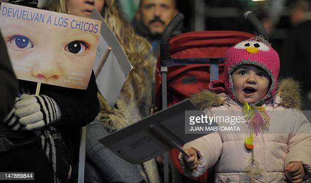 A child cheers as people and members of human rights organizations hold signs as they watch on a giant screen outside the court the reading of the...