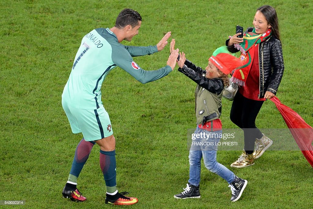 TOPSHOT - A child cheers Portugal's forward Cristiano Ronaldo (L) at the end of the Euro 2016 round of sixteen football match Croatia vs Portugal, on June 25, 2016 at the Bollaert-Delelis stadium in Lens. / AFP / FRANCOIS