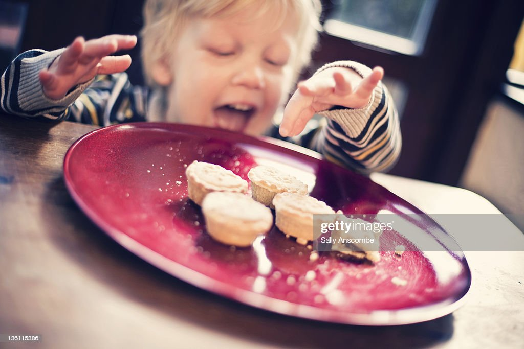 Child choosing  mince pie to eat : Stock Photo