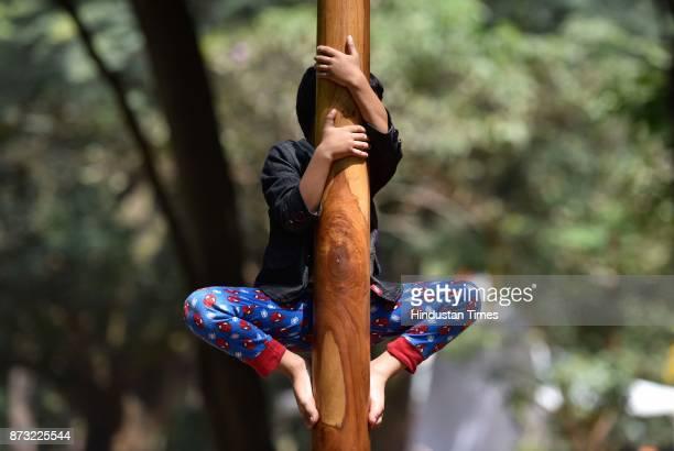 A child climbing on a Mallakhamb pole during Makkala Hanna Children Festival at Cubbon Park on November 12 2017 in Bengaluru India Karnataka...