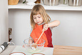 three years old child with orange and red apron making and cooking a sponge cake at kitchen home, stirring yogurt with wooden spoon in glass bowl