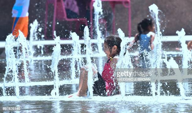 A child cools off at the Grand Park splash pad in downtown Los Angeles California on June 19 amid a Southern California heatwave with highs again...