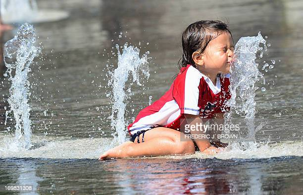 A child cools off in a water fountain plaza at Grand Park in downtown Los Angeles California on June 2 where summer afternoon temperatures reached 75...