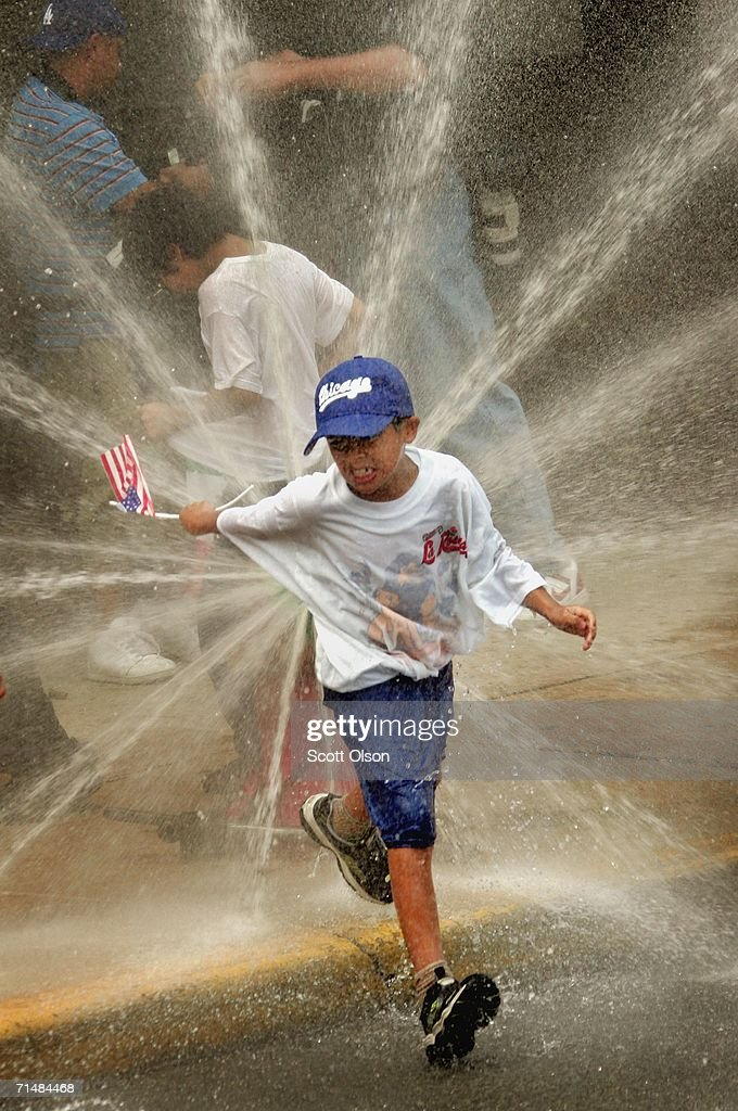 A child cools off with spray from a fire hydrant during an immigrant rights march July 19, 2006 in Chicago, Illinois. About 10,000 people marched from the city?s west side, through downtown, to Grant Park calling for a halt to deportations while Congress works on an immigration reform package.